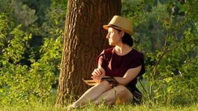 Educação e negócio - 3 Menina que senta-se no parque sob uma árvore verde e que trabalha em uma tabuleta imagem de stock