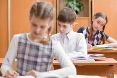 Educação, escola, aprendizagem e conceito das crianças - o grupo de escola caçoa com penas e livros de texto que escreve o teste  fotografia de stock