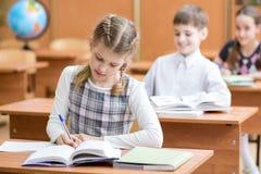 Educação, escola, aprendizagem e conceito das crianças - o grupo de escola caçoa com penas e livros de texto que escreve o teste  foto de stock royalty free