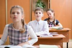 Educação, escola primária, aprendizagem e conceito dos povos - o grupo de escola caçoa o teste da escrita na sala de aula fotos de stock royalty free