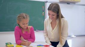 Educação individual, tutor experiente que ensina a menina esperta na tabela perto do quadro-negro na sala de aula da escola filme