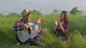 A educação musical, paizinho engraçado feliz ensinar o filho jogar a guitarra quando aplausos e risos ao relaxar no piquenique da vídeos de arquivo