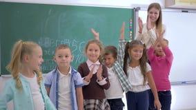 A educação primária, crianças da escola com olhar do professor na câmera e aplaude então no fundo do quadro-negro vídeos de arquivo