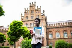 Educação, tecnologia e conceito dos povos - estudante afro-americano fêmea de sorriso com saco e para levar embora fora o copo de fotografia de stock royalty free