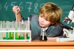 Educa??o escolar Explore mol?culas biol?gicas Bebê do gênio da criança Menino perto do microscópio e dos tubos de ensaio na escol fotografia de stock royalty free