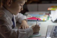 Educación casera Trabajo casero después de la escuela Muchacho con la pluma que escribe palabras inglesas a mano en el papel blan Imágenes de archivo libres de regalías