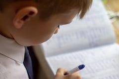 Educación casera Trabajo casero después de la escuela Muchacho con la pluma que escribe palabras inglesas a mano en el papel blan Fotos de archivo libres de regalías