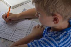 Educación casera Trabajo casero después de la escuela Muchacho con la pluma que escribe la prueba inglesa a mano en el papel blan Fotografía de archivo libre de regalías