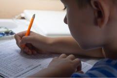 Educación casera Trabajo casero después de la escuela Muchacho con la pluma que escribe la prueba inglesa a mano en el papel blan Fotografía de archivo