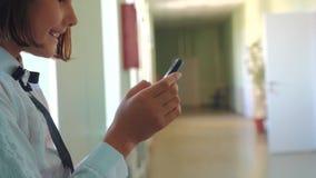 Educación de la colegiala con smartphones en el concepto de la escuela Adolescencia de la chica joven y smartphone con que hace u almacen de video