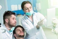 Educación de la odontología Profesor de sexo masculino del doctor del dentista que explica procedimiento del tratamiento foto de archivo libre de regalías
