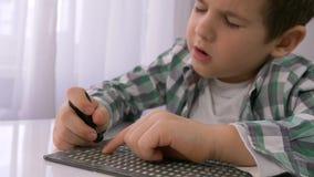 Educación de niños ciegos, niño pequeño enfermo que aprende escribir la fuente de caracteres Braille en la tabla en brillante almacen de metraje de vídeo