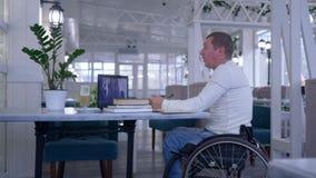 Educación distante, estudiante inválido en la silla de ruedas que hace notas en el cuaderno que mira la pantalla del ordenador po almacen de metraje de vídeo