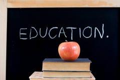 EDUCACIÓN en la pizarra con la manzana y los libros Imagen de archivo libre de regalías