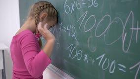 Educación escolar, situación femenina trastornada del alumno cerca de la pizarra con ejemplos de las matemáticas almacen de video