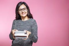 Educación, felicidad y concepto de la gente - imagen del estudiante feliz con la pila de libros sobre fondo rosado imágenes de archivo libres de regalías