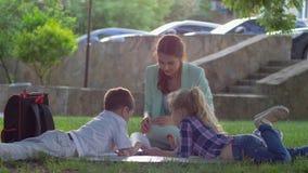 Educación moderna, pequeños niños que escuchan la sentada fascinadora de lectura del libro de la mujer en hierba verde en natural almacen de metraje de vídeo