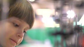 Educación, niñez, emoción, expresión y concepto de la gente El muchacho mira la máquina del funcionamiento del interior de los má metrajes