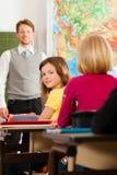 Educación - profesor con el alumno en la enseñanza de la escuela Foto de archivo libre de regalías