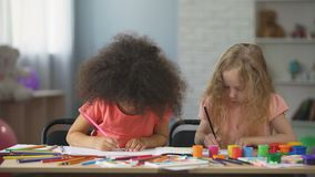 Educación temprana, dos niños femeninos multi-étnicos que dibujan con los lápices coloridos almacen de metraje de vídeo