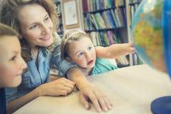 Educación Vista lateral de los niños que señalan en el globo en classro Fotos de archivo