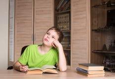 Educación y concepto de la escuela Muchacho adolescente que lee un libro en casa Imagen de archivo libre de regalías