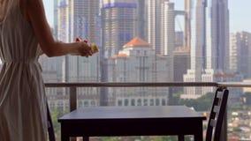 Educadora da jovem mulher que prepara o café da manhã em um balcão que negligencia os arranha-céus do centro da cidade video estoque
