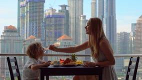A educadora da jovem mulher tem o café da manhã com um menino em um balcão que negligencia os arranha-céus do centro da cidade video estoque