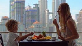 A educadora da jovem mulher tem o café da manhã com um menino em um balcão que negligencia os arranha-céus do centro da cidade filme