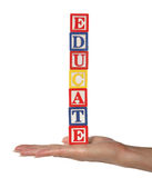 Educate. A woman holding toy blocks spelling educate Royalty Free Stock Photo