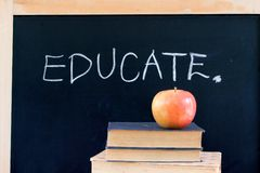 EDUCATE on chalkboard with apple & books. EDUCATE written on chalkboard with red apple & books royalty free stock image