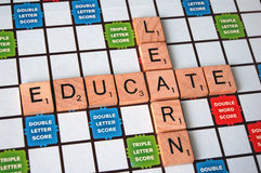 Educate and Learn. The words educate and learn on a scrabble board Royalty Free Stock Photo