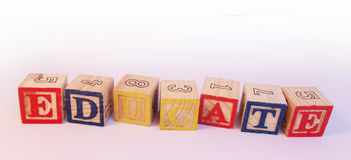 Educate spelled on preschool alphabet blocks. Extreme close up of the word educate spelled with preschool alphabet blocks Royalty Free Stock Photography