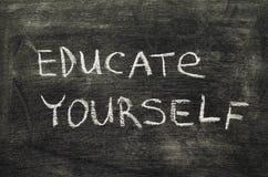 Educate yourself. Phrase handwritten on school blackboard stock photography