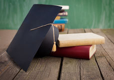 Educate yourself. Books and graduation cap on table Stock Images