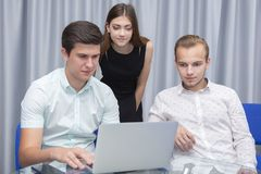 Educated advertisers, two guys and girl develop and place ads, conduct marketing research royalty free stock photo