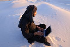 Educated Arab student uses laptop and works sitting on sand amid. Joyous male Arab sits on sand at computer. young man engaged in scientific work or writes royalty free stock images