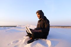 Educated Arab student uses laptop and works sitting on sand amid. Joyous male Arab sits on sand at computer. young man engaged in scientific work or writes stock photos
