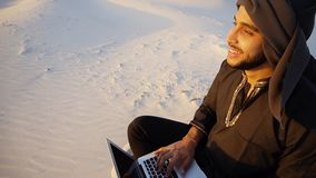 Educated Arab student uses laptop and works sitting on sand amid. Joyous male Arab sits on sand at computer. young man engaged in scientific work or writes royalty free stock photography