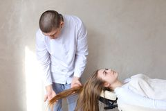 Handsome guy massage therapist doing head massage for girl clien. Educated cosmetologist conducts procedure to relieve tension in head and gives advice on care Stock Photos