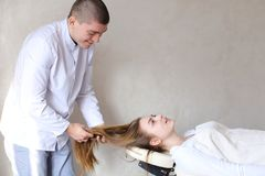 Handsome guy massage therapist doing head massage for girl clien. Educated cosmetologist conducts procedure to relieve tension in head and gives advice on care Stock Photography