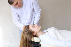 Handsome guy massage therapist doing head massage for girl clien. Educated cosmetologist conducts procedure to relieve tension in head and gives advice on care Royalty Free Stock Images