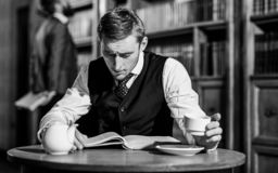 Educated elite or aristocrats spend leisure in library. Intelligent, men in suit with good manners hold cup of tea. Aristocrats and elite concept. Young men stock photos