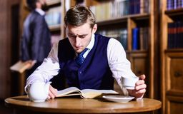 Educated elite or aristocrats spend leisure in library. Intelligent, men in suit with good manners hold cup of tea. Aristocrats and elite concept. Young men Royalty Free Stock Photo