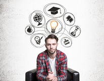 Educated man with ideas. Educated young man with bright ideas. Casual guy sitting on concrete background with lamp and education related drawings royalty free stock photos