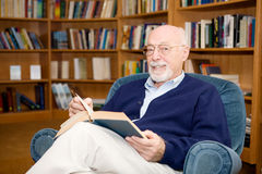 Educated Senior Man. Intellectual looking senior man reading a book in the library stock images