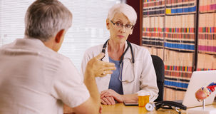 Educated woman doctor talking with patient in her office Stock Image