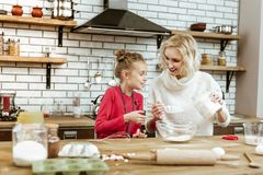 Educated woman with wavy hairs showing her curious daughter. During cooking process. Educated women with wavy hairs showing her curious daughter receipt of dough royalty free stock photography