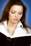 Educated young woman. Pretty young woman reading a book Royalty Free Stock Photography