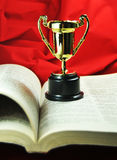Education. Metaphor with award and open book Stock Images